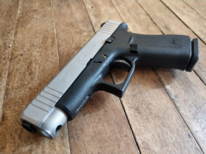 Two-tone silver and black Glock 48 slimline concealment semi-automatic pistol lying on a rustic hardwood floor.