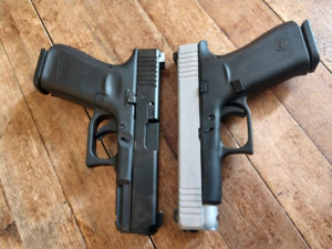A two-tone silver and black Glock 48 lying slide-to-slide with a Gen 5 Glock 19 for a comparison of size