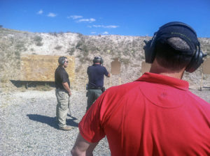 Three men standing on an outdoor shooting range, all with eye and ear protection. The man in the red polo is the range safety officer (RSO). He is supervising an instructor in a black polo shirt and khaki tactical pants work with a student wearing a navy blue polo shirt who is aiming a stainless-steel semi-automatic pistol downrange at a cardboard silhouette target, behind which is an earthen berm and bright blue sky.