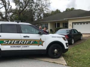 White Hernando County (Florida) Sheriff's Department patrol SUV parked at the end of a residential driveway where it is blocking in a dark sedan and a large pickup truck. An older white man with glasses and a bushy gray mustache faces the camera from the far side of the cruiser while a young white male with short red hair and a burgundy shirt stands nearby with his back to the camera.