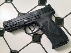 A black Smith & Wesson M&P model 9mm semi-automatic pistol lying on a white tile floor with black grouting and parquet.