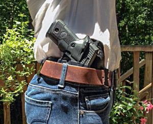 The grips of a large black semi-automatic pistol sticking out of the waistband of a slender gentleman's jeans. His white dress shirt is tucked between his body and the holstered firearm. A reddish brown belt is supporting the inside-the-waistband holster.
