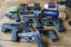 A variety of Ruger, Beretta and Glock pistols and random boxes of ammunition lying on a weather plank deck. Both semi-automatic pistols and revolvers are represented.