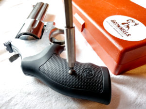 The silver shaft of a BROWNELLS gunsmithing screwdriver has been inserted into the grip screw of a Smith & Wesson Model 686 Plus .357 Magnum revolver as the gun lies on a white drop cloth beside an orange BROWNELLS box