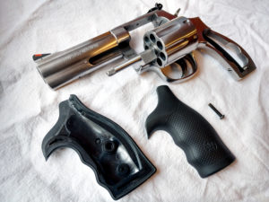 A stainless-steel Smith & Wesson Model 686 Plus, seven-shot .357 magnum revolver field stripped to its component parts for cleaning