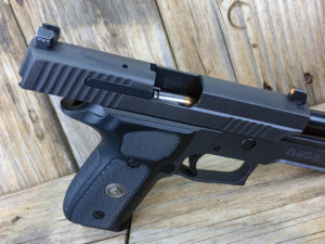 A black SIG Sauer P229 with the action open, showing a nickel and copper round being fed from the magazine into the chamber.