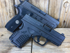 A black Springfield Armory XD-S striker-fired pistol and a black SIG Sauer P229 semi-automatic handgun propped up on a background of weathered timbers on an outside deck.