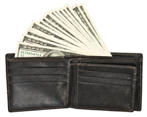 Several hundred-dollar bills of U.S. currency fanned out from the bill pocket of a black leather wallet