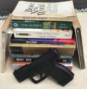 A black Walther handgun propped up against a stack of classic literature