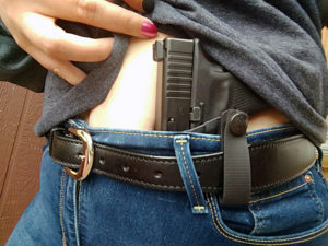 A white woman uses her right hand to lift the bottom hem of a gray shirt to reveal the grips of a black Glock 9mm pistol worn in an AIWB on her left side. The black leather holster is strapped to her black belt in the dark blue denim jeans