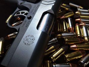 Dramatically lit photo of a Ruger SR1911 9mm semi-automatic handgun lying atop a pile of ammunition comprised of several brands and styles of 9mm rounds.