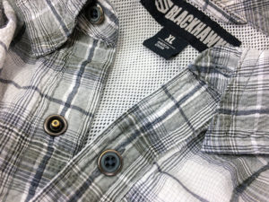 Close-up f a gray and brown plaid concealment shirt from BLACKHAWK featuring snaps that are disguised as buttons and a white mesh lining.