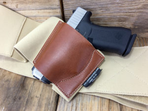 The Galco Underwraps Belly Band consists of a brown leather holster pocket sewn onto a tan elastic band. A small two-tone silver and black semiautomatic compact pistol is encased in the brown leather holster pocket.