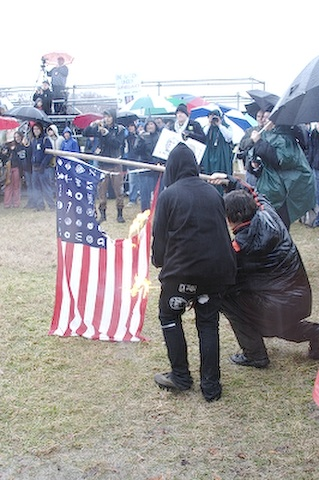 On a rainy day, protestors dressed in black hooded jackets and dark attire burn an American flag which has been emblazoned with corporate logos in place of the usual 50 stars.