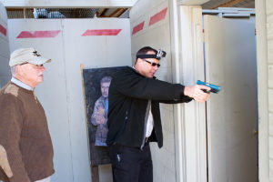"""Two adult white men use blue training pistols as they go through a """"shoot house"""" simulation. One man stands aside to observe while the other, dressed in dark clothing with a headlamp and blue-and-black pistol drawn, aims at a target through an open doorway. A """"perp"""" paper target stands against a white drywall behind the men."""