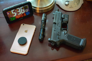 A typical home-defense plan night stand set-up including a digital alarm clock, the base of a brass lamp, a Homedics device, a pink iPhone with a magnet mount, a small black tactical flashlight with a pocket clip and a black semi-automatic pistol with alight mounted on a rail under the barrel.