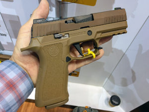 A white male in a red, white and blue plaid shirt displaying a Flat Dark Earth (FDE) SIG Sauer X-Compact 9mm compact concealed carry pistol in the flat of his open palm.