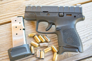 Black Beretta APX carry subcompact concealed carry pistol lying on an untreated deck next to an empty magazine and 11 spent 9mm brass casings.