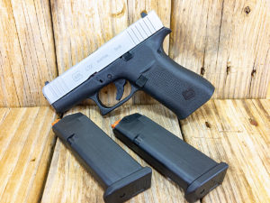 Two-tone silver and black Glock 43X subcompact pistol propped against a backdrop of unstained wood. Two empty Glock magazines lie nearby.