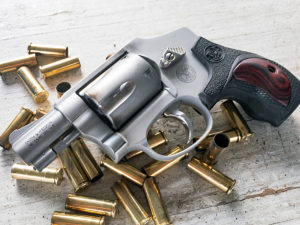 A silver Smith & Wesson .38 Special +P subcompact self-defense revolver with fancy Performance Center grips, lying on a wooden backdrop among a pile of spent .38 Special brass casings.