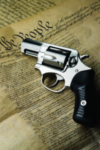 """A silver snub-nosed revolver with black grips lying atop a copy of the United States Constitution, with the muzzle pointed at the """"We"""" in """"We the People."""""""