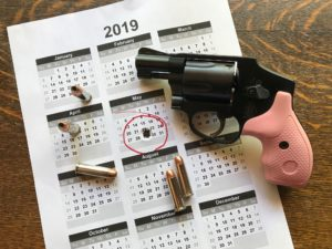 A black Smith & Wesson revolver with pink grips lying beside five hollow-point .38 Special rounds. The backdrop is a white paper 2019 calendar featuring all of the months on one page, with the date Wednesday, May 29, circled in red and shot out by a bullet hole.