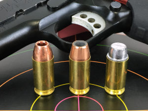 Three rounds of ammo standng atop a target with a handgun lying nearby in the background. The three cartridges have different bullet weights and therefore different velocities.