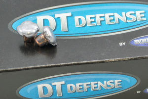Two fully mushroomed DT Defense bullets sitting atop a retail box of cartridges