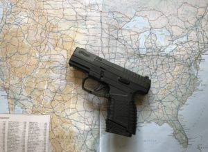 A black Walther PPS semi-automatic concealed carry pistol lying on a map of the United States upon which the state of New Mexico has been outlined in white.