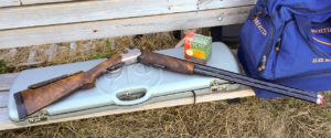 A break-action double-barreled shotgun lying with its action open atop a silver rifle case on a wooden bench. A blue range bag and a box of SUPREMA target ammo are nearby.