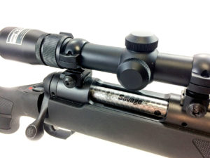 Close-up photo of a Savage Arms hunting rifle with a stainless0steel bolt and a black metal scope.