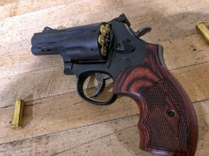 A black .357 Magnum revolver with wooden grips. The cylinder is popped slightly open to reveal the rims of loaded rounds. Two empty cases lie on a wooden deck nearby.
