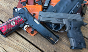 SIG Sauer and Springfield Armory semi-automatic pistols resting on a wooden deck atop a pile of holsters, including one Galco.