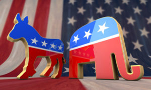 Star-spangled wooden cut-outs of a donkey and an elephant, symbolizing the Democratic and Republican parties (symbolically acing away from one another) with a large American flag in the background.