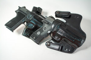 Two black pistols inserted into two different styles of of black leather Galco concealed carry holsters.