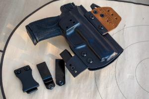 A black Kydex Clinger concealed carry holster alongside several belt clip options.