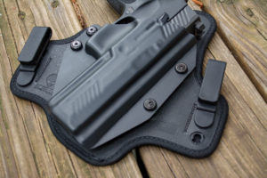 Close-up photo of a back semi-automatic pistol inside a black Alien Gear hybrid Kydex and Neoprene IWB concealed carry holster.