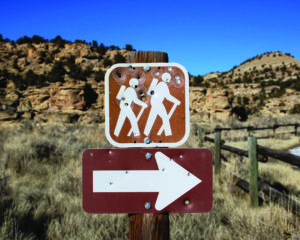 A square brown Forest Service sign depicting two stylized hikers and a large white arrow pointing to the right to indicate the start of a hiking trail. Both signs are full of bullet holes. The arid landscape and weathered rail fence in the background denotes that the sign stands in the Southwestern portion of the United States.