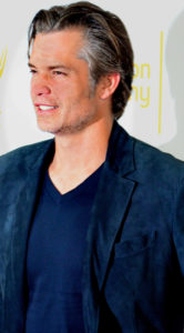 Actor Timothy Olyphant in a blue V-neck T-shirt and blue blazer squinting into the light of media cameras.