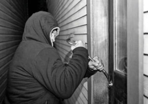 Black and white photo of a man in a hooded jacket using a crowbar to pry open a door. The setting appears to be a narrow walkway between two houses.