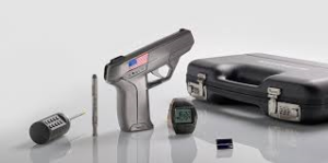 A small gray smart gun emblazoned with American flag graphics standing beside an RFID watch and a hard-sided case.