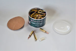 An open canister of bulk Fiocchi .223 Remington ammunition. Three stray rounds lie on the tabletop next to the canister, plastic lid and cardboard gasket.