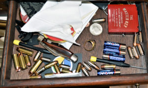 "A ""junk"" drawer littered with batteries, a pocket knife, a class ring, a screwdriver, some pocket change and a handful of various handgun ammunition cartridges."