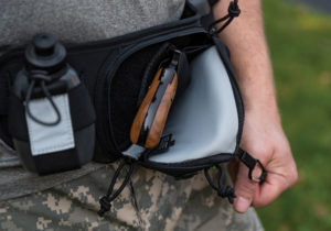 A man in digicam pattern pants uses his left thumb to pull open a concealed pocket in his fanny pack. The grips of a handgun can be seen inside the pocket, tucked into a black nylon holster.