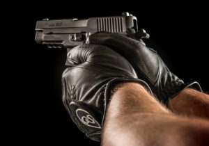 A man uses both hands to aim a black Sig Sauer semi-automatic pistol. He is wearing black leather gloves and the external hammer of the firearm is cocked back, ready to fire.