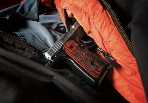The wooden grips of a SOLO concealed carry pistol emerging from the interior pocket of a winter jacket laid out over a gray shirt with a USCCA logo