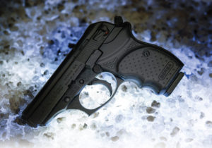 A small black Bersa concealed carry pistol lying in a pile of simulated snow and ice.