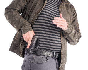 A man in a black and gray striped sweater, charcoal trousers and a faded black denim jacket uses his right hand to draw a semi-auto pistol from a black leather IWB holster clipped to his black leather belt. The man's left hand is close to his solar plexus.