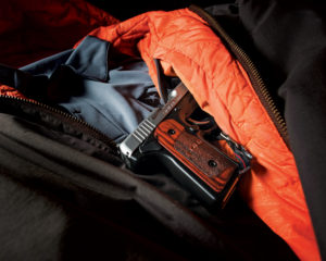 The wooden grips of a stainless-steel semi-auto pistol emerge from the inside-left chest pocket of a military-style flight jacket which has been laid down on a table. A gray USCCA polo shirt is also laid out inside the jacket.