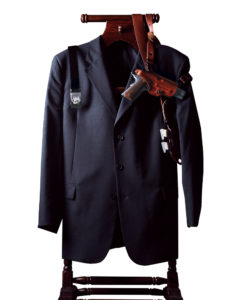 A navy blue three-button sport coat hanging on a wooden rack. There is a black web belt with a silver USCCA buckle hanging down over one shoulder and a brown leather shoulder holster is draped across the collar and shoulders. The holster contains a 1911-style pistol and two spare magazines.